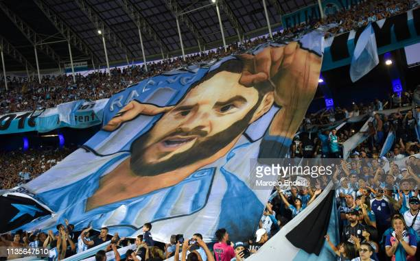 Fans of Racing Club hold a flag in homage to the captain of their team Lisandro Lopez during a match between Racing Club and Defensa y Justicia as...