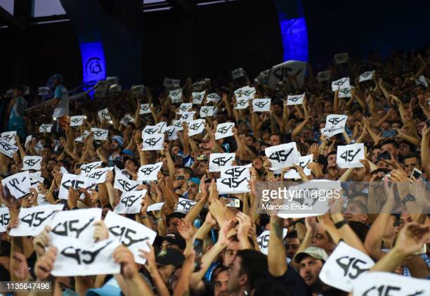Fans of Racing Club hold banners in homage to the captain of their team Lisandro Lopez during a match between Racing Club and Defensa y Justicia as...