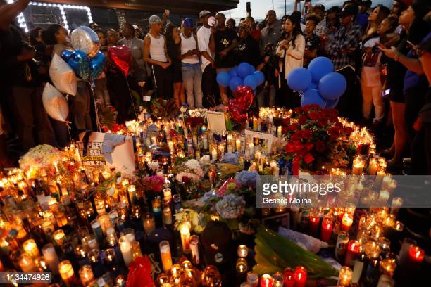 Fans of rapper Nipsey Hussle gather and pay their respects at a makeshift memorial in the parking lot of his Marathon Clothing store April 1 2019 in...