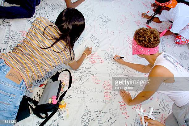 Fans of RB singer Aaliyah Haughton write sentiments on a giant sheet of paper during a memorial candle light vigil August 27 2001 in Detroit Michigan...