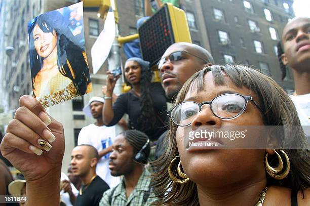 Fans of RB singer Aaliyah watch a horsedrawn carriage carry her coffin towards St Ignatius Loyola Church August 31 2001 during her funeral in New...