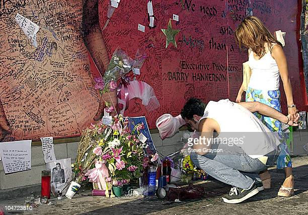 Fans of RB singer/actress Aaliyah looks on at a record store mural of the late singer in what has a become shrine dedicated to her after her death in...