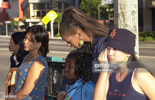 Fans of RB singer/actress Aaliyah looks on at a record store mural of the late singer in what has become a shrine dedicated to her after her death in...