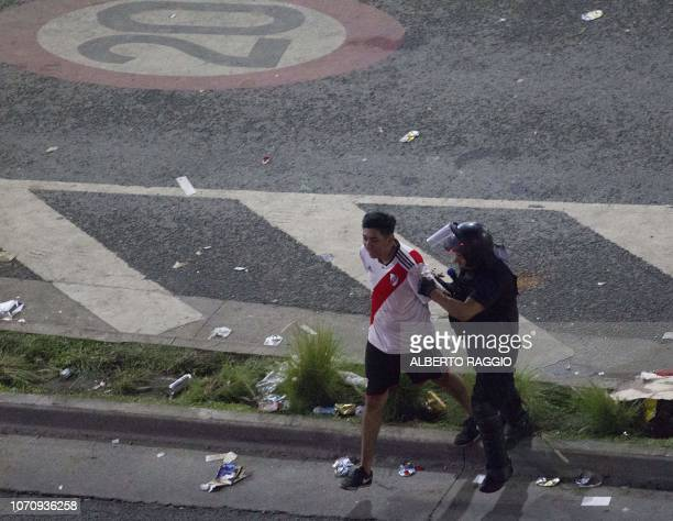 A fans of River Plate is detained by riot police at the Plaza de la Republica in Buenos Aires Argentina after the team won the allArgentine Copa...