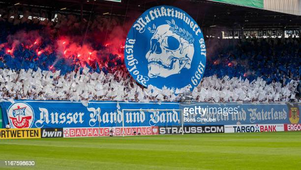 Fans of Rostock burn flares during the DFB Cup first round match between Hansa Rostock and VfB Stuttgart at Ostseestadion on August 12 2019 in...