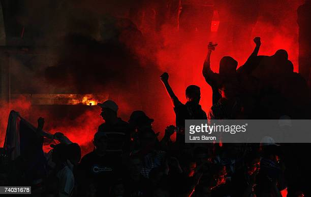 Fans of Rostock light a fire during the Second Bundesliga match between Rot Weiss Essen and Hansa Rostock at the Georg Melches stadium on April 30...