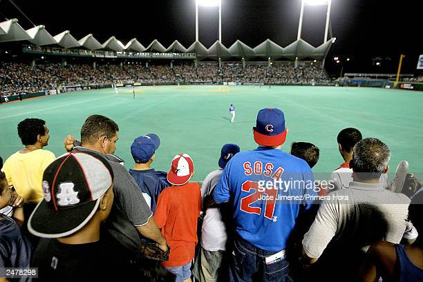 Fans of Sammy Sosa of the Chicago Cubs stand in the right field bleachers to catch a glimpse of their hero as the Cubs play against the Montreal...