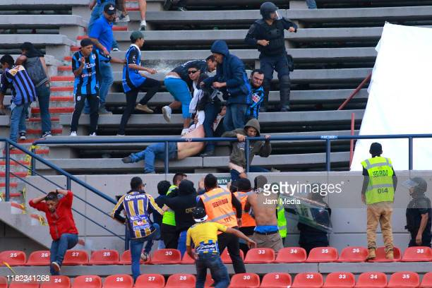 Fans of San Luis and Queretaro fight in the stands during the 14th round match between Atletico San Luis and Queretaro as part of the Torneo Apertura...