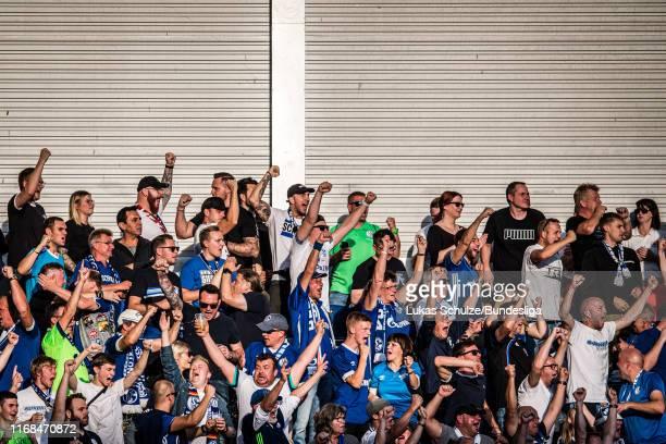 Fans of Schalke celebrate their team's first goal during the Bundesliga match between SC Paderborn 07 and FC Schalke 04 at Benteler Arena on...