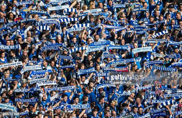 Fans of Schalke hold their scars during the Bundesliga match between FC Schalke 04 and Borussia Dortmund at VeltinsArena on April 1 2017 in...