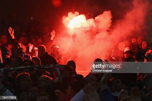 Fans of Schalke ignite smokebombs during the Bundesliga match between Borussia Dortmund and FC Schalke 04 at Signal Iduna Park on November 26 2011 in...