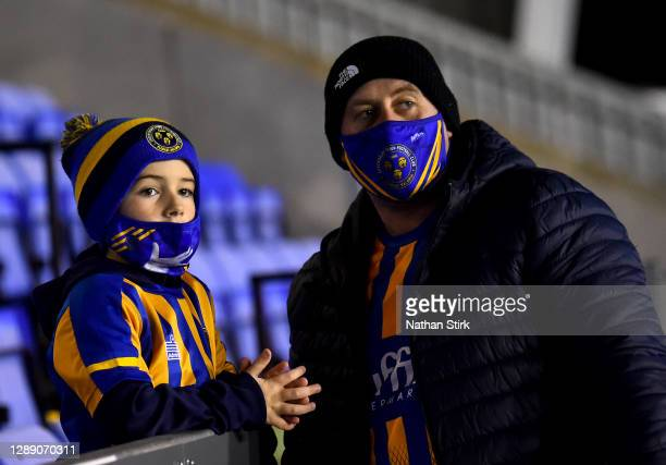 Fans of Shrewsbury Town look on from inside of the stadium wearing fans masks during the Sky Bet League One match between Shrewsbury Town and...