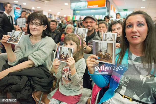 Fans of Stadio hold copies of their CD during the presentation of their new album 'Miss Nostalgia' on February 17 2016 in Turin Italy
