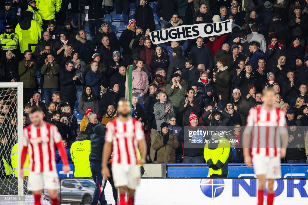 Fans of Stoke City hold up a banner which reads Hughes Out during the Premier League match between Huddersfield Town and Stoke City at John Smith's Stadium on December 26, 2017 in Huddersfield, England.