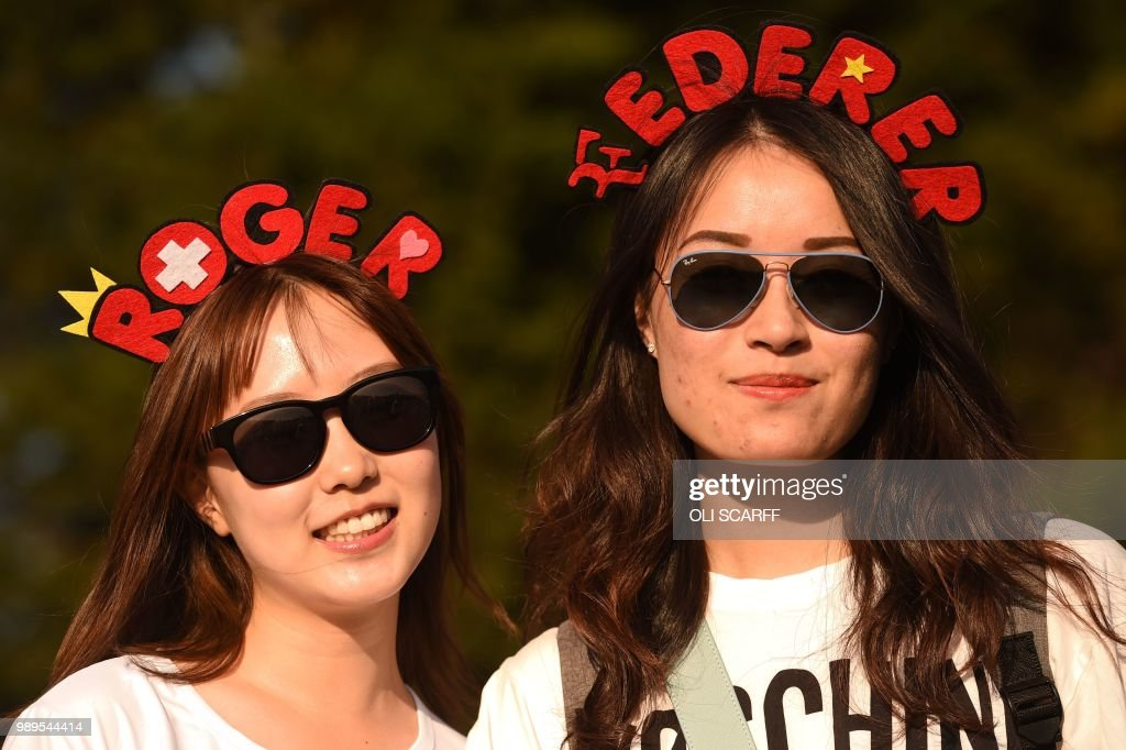 TOPSHOT - Fans of Swiss player Roger Federer poses as they queue for tickets outside The All England Tennis Club in Wimbledon, southwest London, on July 2, 2018, on the first day of the 2018 Wimbledon Championships tennis tournament. (Photo by Oli SCARFF / AFP) / RESTRICTED