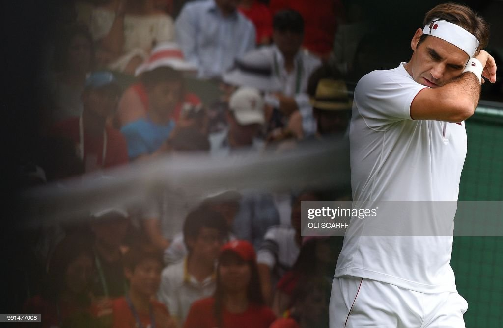 TOPSHOT - Fans of Switzerland's Roger Federer are reflected in a television camera as he plays against Slovakia's Lukas Lacko during their men's singles second round match on the third day of the 2018 Wimbledon Championships at The All England Lawn Tennis Club in Wimbledon, southwest London, on July 4, 2018. (Photo by Oli SCARFF / AFP) / RESTRICTED