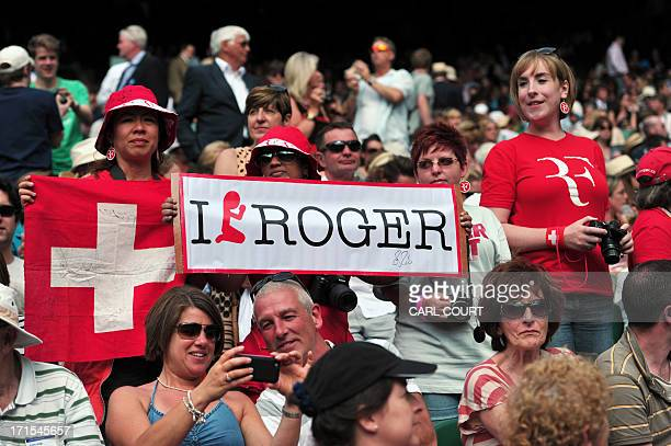 Fans of Switzerland's Roger Federer hold banners and flags as Federer plays against Ukraine's Sergiy Stakhovsky during their second round men's...