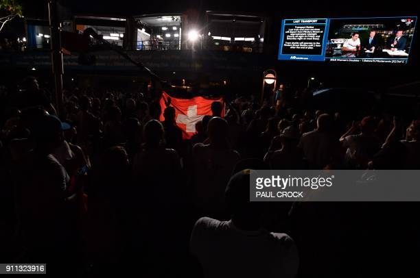 Fans of Switzerland's Roger Federer holds the Switzerland flag as they watch him being interviewed on a big screen after he beat Croatia's Marin...