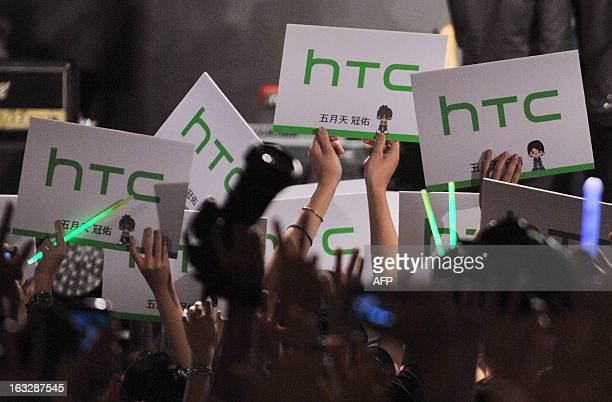 Fans of Taiwan's pop music group Mayday hold signs of HTC smartphone maker during a press conference in Taipei on March 7 2013 HTC unveiled their...