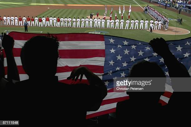 Fans of Team USA hold up an American Flag during the National Anthem before the Round 2, Pool 2 Game of the World Baseball Classic against Team...