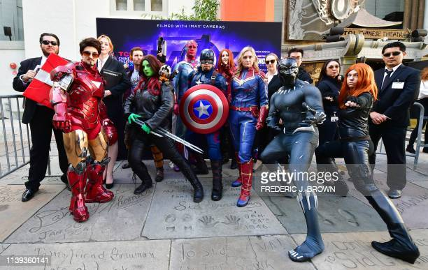 Fans of the Avengers strike a pose while dressed in costumes for a costume contest before the first screening of Avengers Endgame at the TCL Chinese...