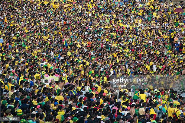 Fans of the Brazilian football team watch a match on a giant screen in the Fan Fest area in Porta Negro on June 17 2014 in Manaus Brazil Brazil the...