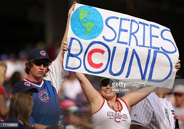 Fans of the Chicago Cubs cheer on their team clinching the National League West division during against the Cincinnati Reds at Great American...