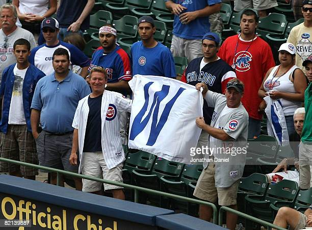 Fans of the Chicago Cubs hold up a win flag along the first baseline after the Cubs complete a four game sweep of the Milwaukee Brewers at Miller...