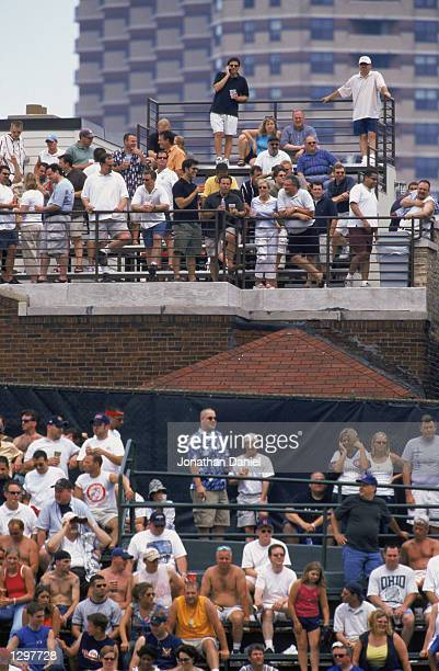 Fans of the Chicago Cubs sit on the rooftop of a building across Clark Street from the stadium in right field during the MLB game against the Texas...