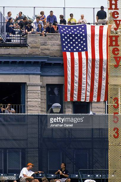 Fans of the Chicago Cubs sit on the rooftop of a building with an American flag draped over it across Clark Street from the stadium in right field...