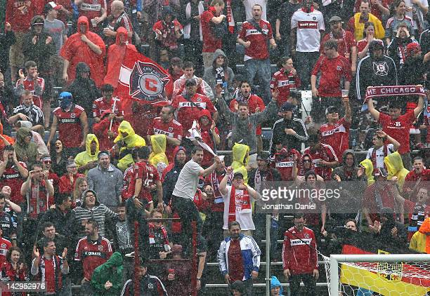 Fans of the Chicago Fire cheer during a thunderstorm as the Fire take on the Houston Dynamo during an MLS match at Toyota Park on April 15 2012 in...