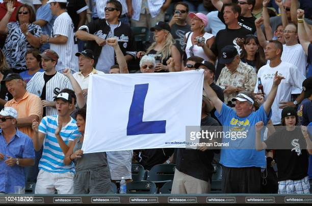 """Fans of the Chicago White Sox hold a """"Loss"""" flag, normally flown at Wrigley Field, after the White Sox beat the Chicago Cubs at U.S. Cellular Field..."""
