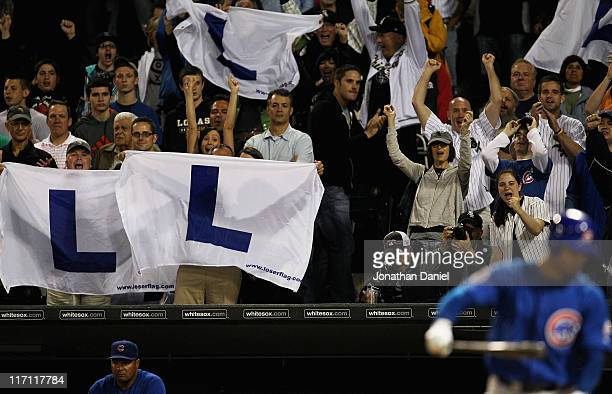 Fans of the Chicago White Sox hold L flags flown at Wrigley Field when the Chicago Cubs lose as Carlos Pena of the Cubs strikes out to end the game...