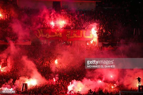 Fans of the Egypt's AlAhly light flares after the first goal during the second leg of the CAF Confederation Cup final football match between Egypt's...