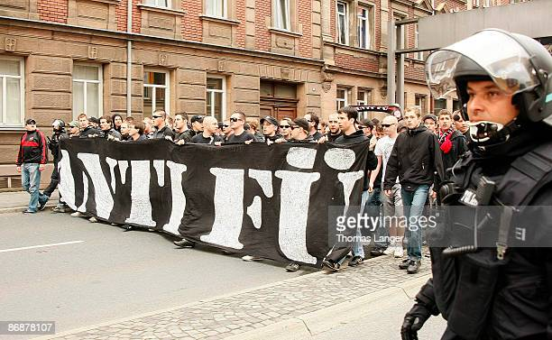 "Fans of the FC Nuernberg hide behind an banner that reads ""ANTI FUE during their walk through Fuerth prior to the Second Bundesliga match between..."