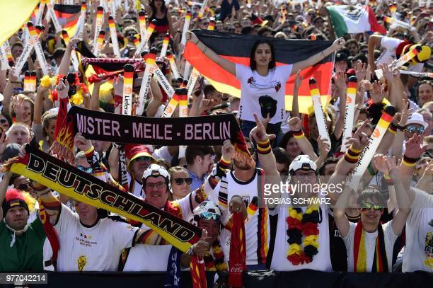 """Fans of the German team cheer during a public viewing event at the """"Fanmeile"""" area in front of Berlin's landmark Brandenburg Gate on June 17 before..."""