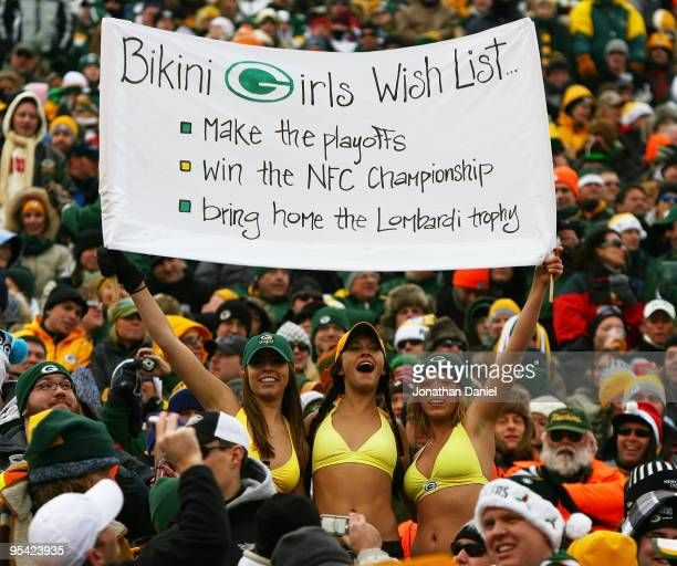 Fans of the Green Bay Packers hold a sign and wear bikini's in below freezing weather during a game between the Packers and the Seattle Seahawks at...