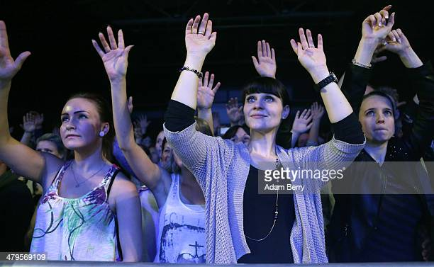 Fans of the group Soehne Mannheims cheer during a concert by the band at Columbiahalle on March 19 2014 in Berlin Germany