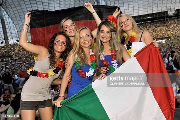Fans of the Italian and German teams pose with national flags as they watch the Euro 2012 football championships semifinal match Germany vs Italy at...