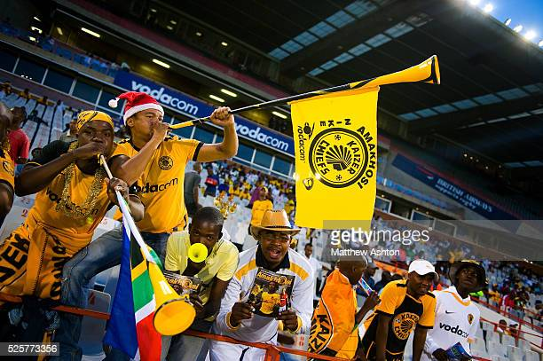 Fans of the Kaizer Chiefs wearing a makarapa a customised miner's hard hat / fan helmet and blowing a vuvuzela trumpet horn