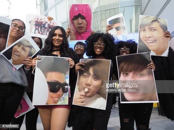 Fans of the Korean boy band group BTS pose with photos of their idols outside the 2017 American Music Awards November 19 2017 at the Microsoft...