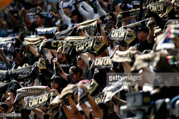 Fans of the Los Angeles FC hold up their scarves ahead of a game against the Seattle Sounders at Banc of California Stadium on April 21 2019 in Los...