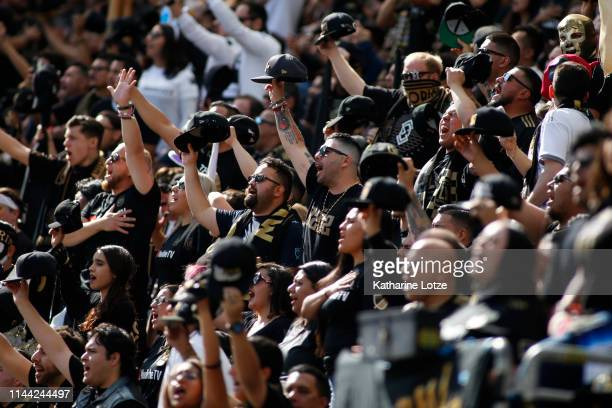 Fans of the Los Angeles FC sing the national anthem ahead of a game against the Seattle Sounders at Banc of California Stadium on April 21 2019 in...