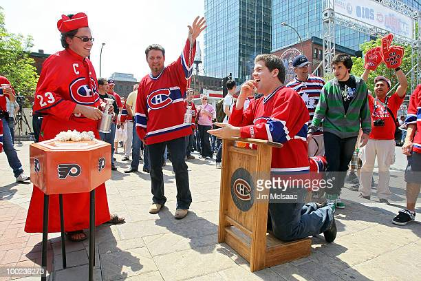 Fans of the Montreal Canadiens pretend to receive communion prior to Game 4 of the Eastern Conference Finals during the 2010 NHL Stanley Cup Playoffs...