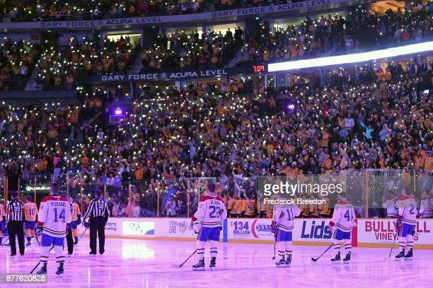 Fans of the Nashville Predators hold their phone lights on with members of the Montreal Canadiens to stand together for a moment of silence to show...
