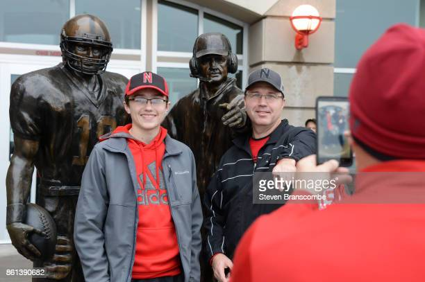 Fans of the Nebraska Cornhuskers have their picture taken by the Tom Osborne statue before the game against the Ohio State Buckeyes at Memorial...