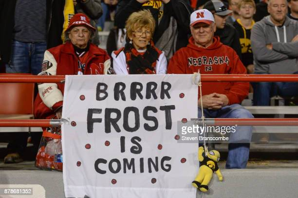 Fans of the Nebraska Cornhuskers sit behind a sign in support of coaching prospect Scott Frost during the game against the Iowa Hawkeyes at Memorial...