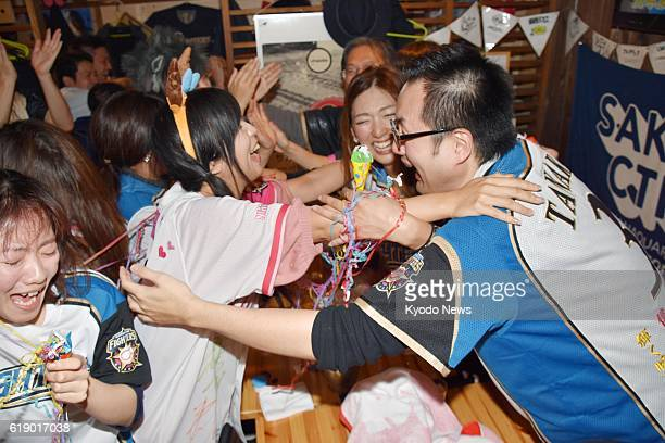Fans of the Nippon Ham Fighters hug each other in Sapporo after the club won its first Japan Series title in 10 years in Hiroshima on Oct 29 2016