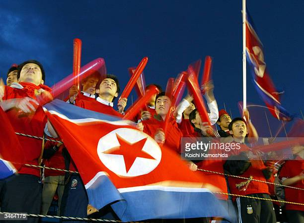 Fans of the North Korean national women's soccer team cheer at the AFC Olympics qualifying tournament semifinal game against Japan at the National...