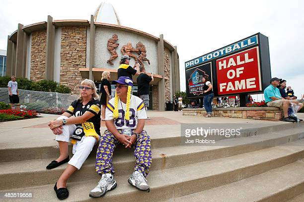 Fans of the Pittsburgh Steelers and Minnesota Vikings sit on the front steps of the Pro Football Hall of Fame prior to the NFL Hall of Fame Game at...
